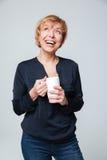 Imagem vertical de rir a mulher idosa com copo imagens de stock