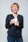 Imagem vertical de rir a mulher idosa que guarda o chá do copo imagem de stock