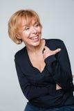 Imagem vertical de rir a mulher idosa que levanta no estúdio fotos de stock
