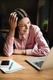 Imagem vertical de rir a mulher moreno que senta-se pela tabela fotos de stock