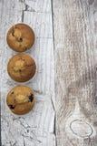 Imagem vertical de três muffin de blueberry em um fundo de madeira fotografia de stock royalty free