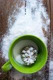 A imagem vertical do copo verde com o cone do pinho no sal olha como a neve no fundo de madeira fotografia de stock royalty free