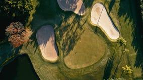 imagen aérea de un curso del campo del golf con una bandera y un agujero y algunas piscinas de la arena y de agua con la hierba h fotos de archivo libres de regalías