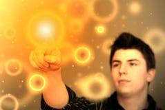 Imagen abstracta - hombre joven que toca el punto flotante anaranjado que brilla intensamente Fotos de archivo libres de regalías