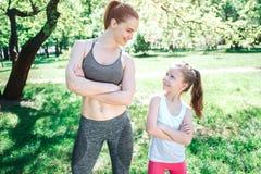 Imagen agradable de la mujer joven y delgada y su de la hija que se colocan en parque Están mirando uno a y la sonrisa Chica Imágenes de archivo libres de regalías