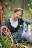 Imagen agradable de una muchacha cerca de la rueda del vintage Fotos de archivo