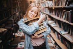 Imagen agradable y caliente de la muchacha atractiva que abraza los libros que ella sostiene en sus manos Ella la ha cerrado los  Foto de archivo