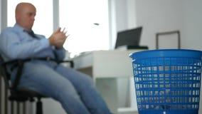 Imagen agujereada del hombre de negocios en la oficina que lanza el documento arrugado sobre cesta de la basura almacen de video