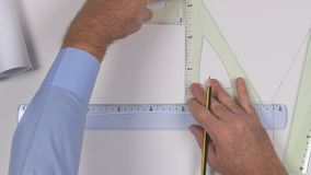 Imagen ascendente cercana con el ingeniero Hands Drawing en un plan de papel usando las herramientas de dibujo almacen de metraje de vídeo