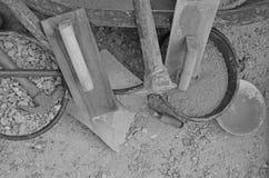 Imagen blanco y negro de herramientas y de materiales del albañil Imagenes de archivo
