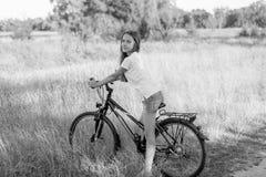 Imagen blanco y negro de la bicicleta del montar a caballo del adolescente en el prado Imagen de archivo