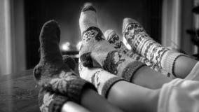 Imagen blanco y negro de la familia que lleva los calcetines de lana hechos punto que se relajan por la chimenea foto de archivo libre de regalías