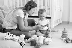 Imagen blanco y negro de la madre joven que juega con su bebé en f Fotografía de archivo libre de regalías