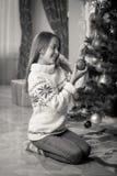Imagen blanco y negro de la muchacha sonriente que adorna el árbol de navidad Imagen de archivo