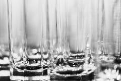 Imagen blanco y negro de los muchos vidrios para las bebidas como fondo abstracto Imagen de archivo