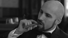 Imagen blanco y negro de un hombre brutal con un cigarro metrajes