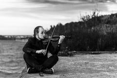 Imagen blanco y negro de un imitar que se sienta en la orilla y que toca el violín al aire libre Imagenes de archivo