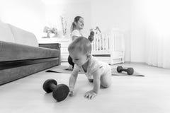 Imagen blanco y negro del bebé que juega con pesas de gimnasia mientras que m Fotos de archivo