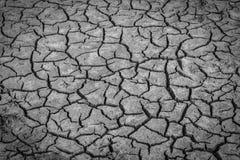 Imagen blanco y negro del fondo de la suciedad agrietada seca del suelo foto de archivo