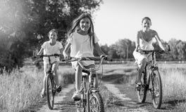 Imagen blanco y negro del montar a caballo joven de la madre en las bicicletas con TW Foto de archivo libre de regalías