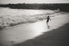 Imagen blanco y negro del niño que corre el la tarde Fotos de archivo