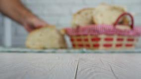 Imagen borrosa con las manos del hombre que ponen el pan en la tabla almacen de metraje de vídeo