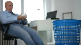Imagen borrosa con un hombre de negocios aburrido Throwing Crumpled Paper en cesta de la basura