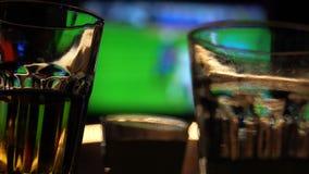 Imagen borrosa de la barra de deporte con la TV y de bebidas en primero plano almacen de video