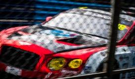 Imagen borrosa de la red y del coche de la malla de la cerca en fondo de la pista Carreras de coches del Motorsport en la carrete Fotografía de archivo