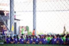 Imagen borrosa de los futbolistas sentarse en fila fotos de archivo libres de regalías