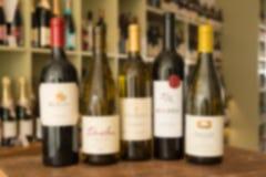 Imagen borrosa de una fila de cinco botellas de vino Imagen de archivo
