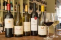 Imagen borrosa de una fila de cinco botellas de vino y copas Imagen de archivo libre de regalías