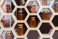 Imagen borrosa, visión a través del vidrio de la ventana de madera de la tienda con los tarros de cristal con la miel Imagenes de archivo