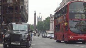 Imagen céntrica de Londres con los coches del tráfico en los taxis viejos de la calle y los autobuses rojos almacen de video