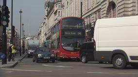 Imagen céntrica de Londres con los coches del tráfico de la calle y los autobuses rojos del autobús de dos pisos almacen de metraje de vídeo