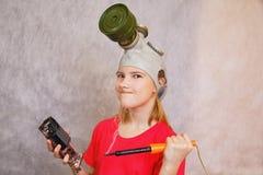 Imagen cómica de una muchacha que quiere terminar la reparación de la electrónica Foto de archivo
