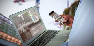 Imagen compuesta 3d del hombre de negocios usando el teléfono móvil y el ordenador portátil fotos de archivo