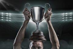 Imagen compuesta 3D del jugador acertado del rugbi que celebra el trofeo imagen de archivo