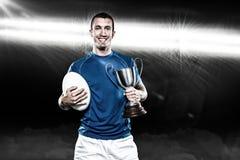 Imagen compuesta 3D del retrato del jugador sonriente del rugbi que celebra el trofeo y la bola imágenes de archivo libres de regalías