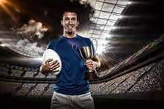 Imagen compuesta 3D del retrato del jugador sonriente del rugbi que celebra el trofeo y la bola fotografía de archivo libre de regalías