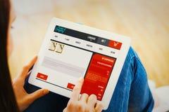 Imagen compuesta de adolescente usando una PC de la tableta que se sienta en el piso Imágenes de archivo libres de regalías