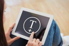 Imagen compuesta de adolescente usando una PC de la tableta que se sienta en el piso Imagen de archivo libre de regalías