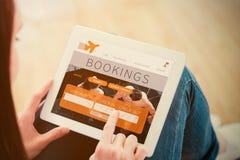 Imagen compuesta de adolescente usando una PC de la tableta que se sienta en el piso Foto de archivo