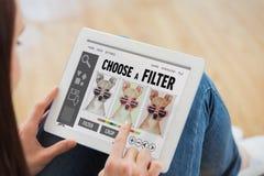 Imagen compuesta de adolescente usando una PC de la tableta que se sienta en el piso Imagenes de archivo