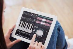 Imagen compuesta de adolescente usando una PC de la tableta que se sienta en el piso Foto de archivo libre de regalías