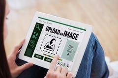 Imagen compuesta de adolescente usando una PC de la tableta que se sienta en el piso Fotografía de archivo
