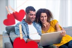 Imagen compuesta de colgar corazones y pares rojos usando un ordenador portátil foto de archivo