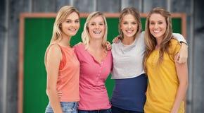 Imagen compuesta de cuatro amigos que se colocan al lado de uno a y de la sonrisa Foto de archivo libre de regalías