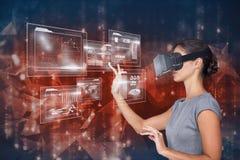 Imagen compuesta de Digitaces de la pantalla futurista conmovedora de la mujer mientras que usa los vidrios de VR Fotografía de archivo libre de regalías
