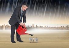 Imagen compuesta de Digitaces de los hombres de negocios de riego del hombre de negocios en lluvia contra ciudad Imagen de archivo